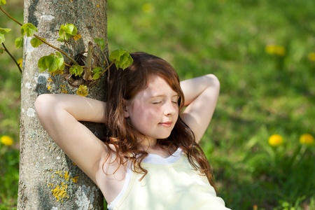 sleeping kid: Young girl with eyes closed leaning on tree trunk in park