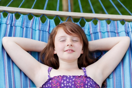 pre teen girl: young girl dreaming in the hammock with hands behind head Stock Photo