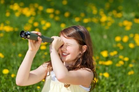 брюнетка: маленькая девочка, глядя через телескоп на зеленом поле