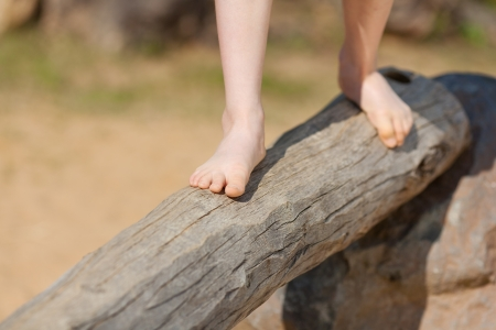 little girl barefoot: Low section of little girl standing on tree trunk in park Stock Photo