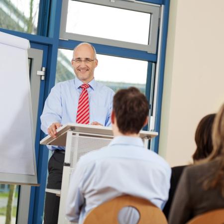 hablar en publico: Retrato de hombre de negocios dando presentación a sus compañeros de trabajo mientras está de pie en el podio en la oficina Foto de archivo