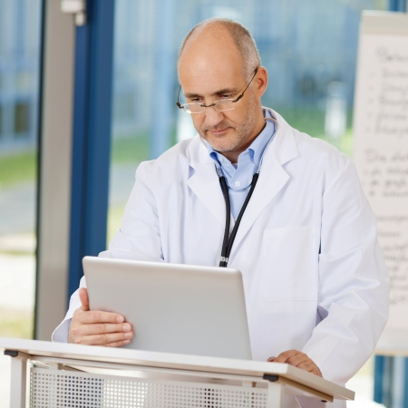 Mature male doctor using laptop at podium in clinic