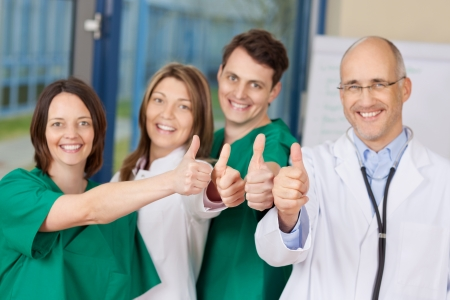Portrait of confident team of doctors gesturing thumbs up sign in hospital photo