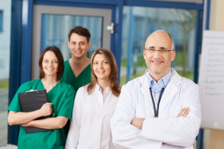 Portrait of confident mature male doctor with team in background at clinic photo