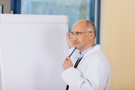 Portrait of thinking mature doctor standing near flipchart in clinic photo