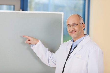 Smiling mature male doctor with finger by flipchart in clinic photo