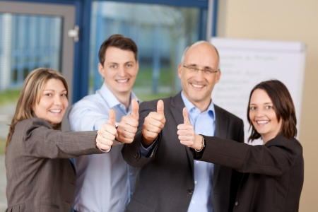 cheering: Portrait of businessmen and businesswomen showing thumbs up sign in office