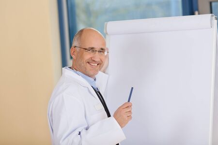 Portrait of happy mature doctor standing near flipchart in clinic photo