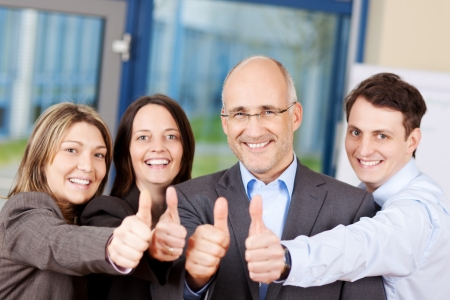 Portrait of businessmen and businesswomen showing thumbs up sign photo