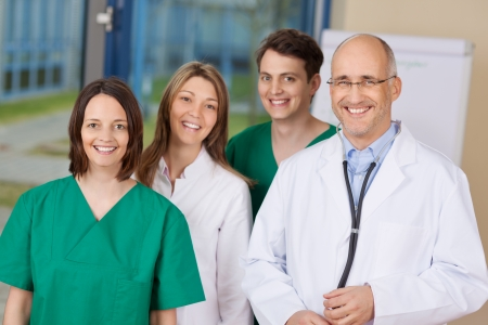 Portrait of happy doctor team standing together in clinic photo