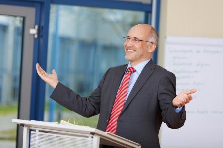 Gelukkig zakenman met opgeheven armen staan op podium in het kantoor Stockfoto