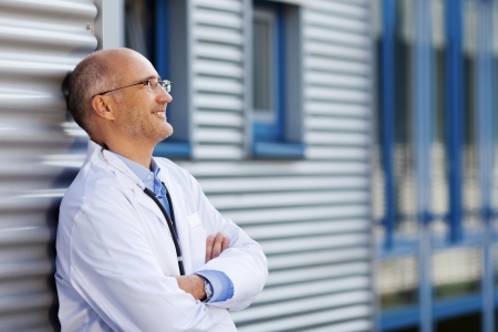 Thoughtful mature doctor with arms crossed smiling while leaning on hospital wall photo