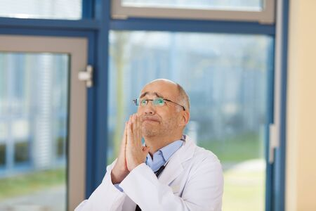 Mature male doctor with hands clasped looking up in clinic photo