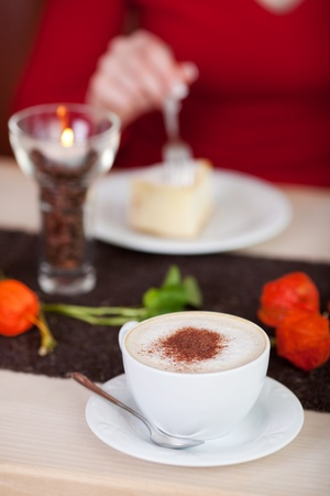 woman having cappuccino and cake in café photo