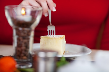 woman eating cheese cake in a café photo