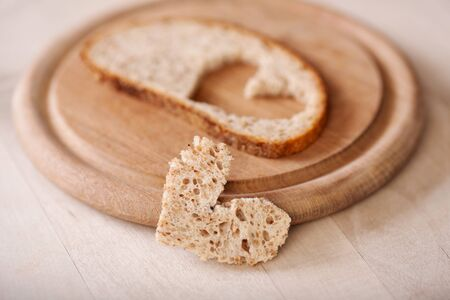 pureness: slice of bread with a heart cut out on wooden plate