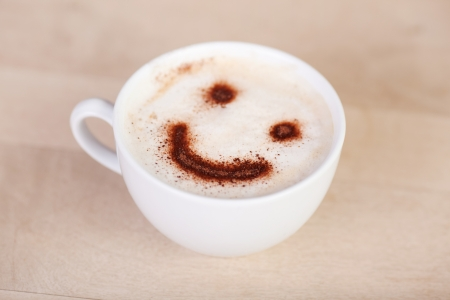 cup of cappuccino with smiley face on millk foam photo