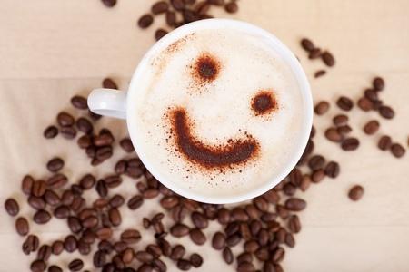 カフェ テーブルの上のコーヒー豆のカプチーノのスマイルのクローズ アップ