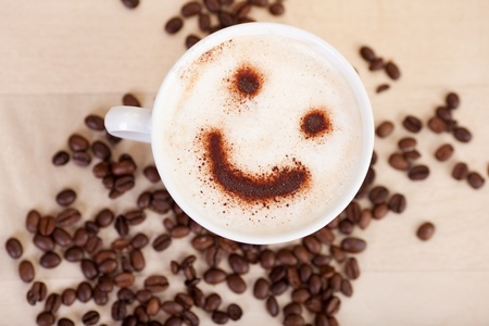 Closeup of smiley face in cappuccino with coffee beans on table at cafe
