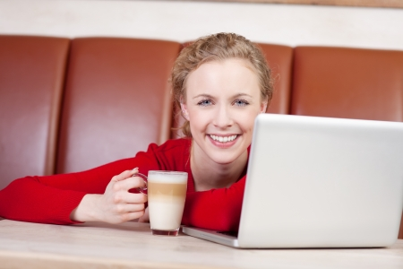 Portrait of happy young woman with laptop holding latte cup in coffee shop photo