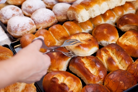 bakery store: Closeup of female bakery workers hand picking up bread with tong