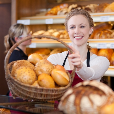 salesgirl: smiling woman passing basket of breads in bakery Stock Photo