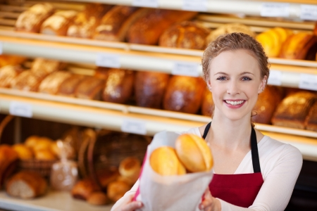 salesgirl: Portrait of happy female worker giving bag of breads in bakery