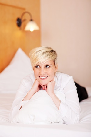 Smiling young beautiful woman with a pillow on her bed photo