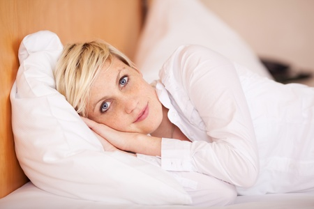 Relaxed young businesswoman sleeping on bed in hotel room Stock Photo - 21217515