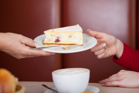 passing: Closeup of female workers hand giving pastry to customer in coffee shop