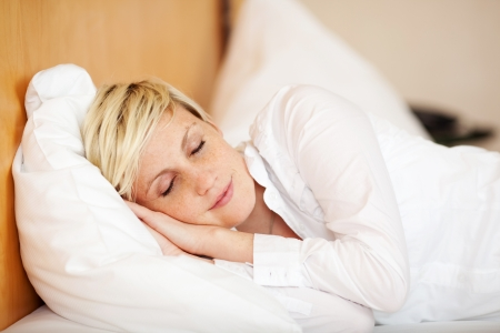 Relaxed young businesswoman sleeping on bed at home, eyes closed photo