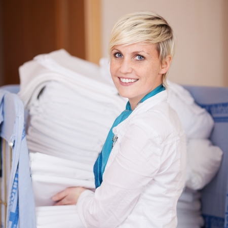 linen fabric: Portrait of young housekeeper stacking sheets in stock room