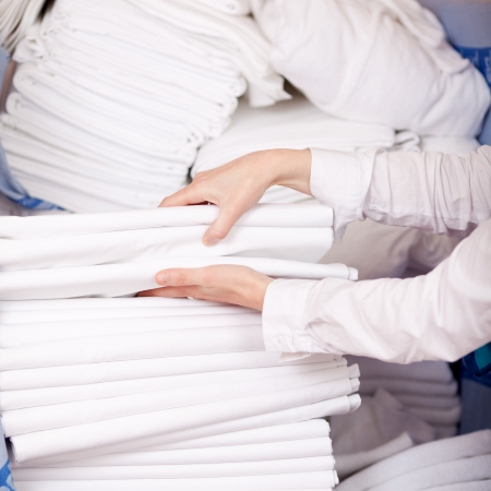 Closeup of female housekeepers hands stacking sheet in stock room photo