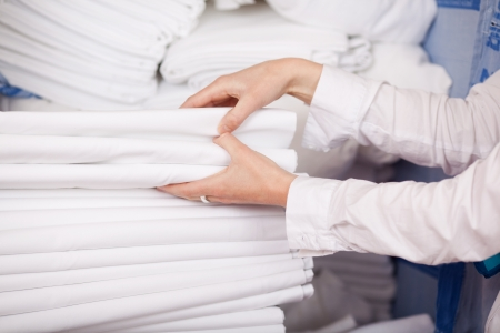 Closeup of white bedsheets stacked in store room of hotel photo