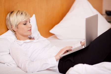 Woman working in hotel room on laptop photo
