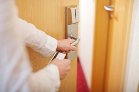 abriendo puerta: Detalle de las manos del ama de llaves femenina sosteniendo cardkey y abrir la puerta de la habitaci�n del hotel Foto de archivo