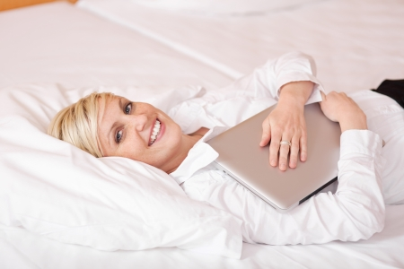 Happy businesswoman with laptop lying on bed photo