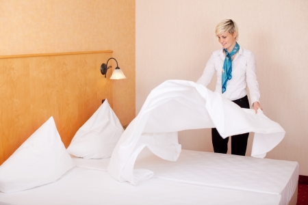 bedclothes: Young female housekeeper making bed in hotel room