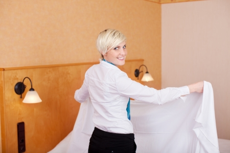Happy female housekeeper making bed in hotel room photo
