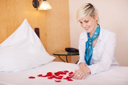 Portrait of happy female housekeeper arranging petals in heart shape photo