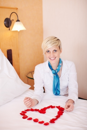 Portrait of happy female housekeeper arranging petals in heart shape on bed photo