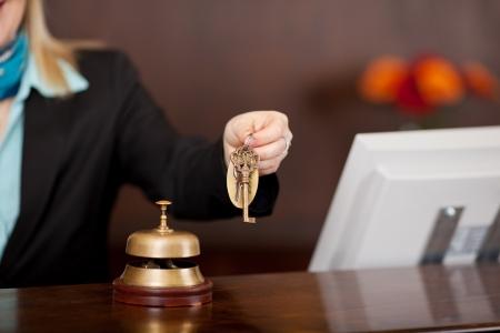 receptioniste passeren kamersleutels over de toonbank