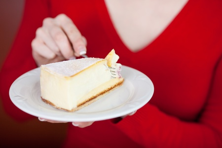 woman´s hand holding a plate with cheese cake photo