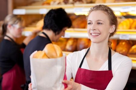 bolsa de pan: sonriente dependienta en la panadería bolsa de pasar de panes