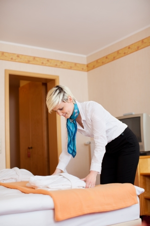 Side view of young housekeeper keeping bathrobe on bed in hotel photo