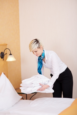 Young female housekeeper keeping bathrobes on bed in hotel room photo