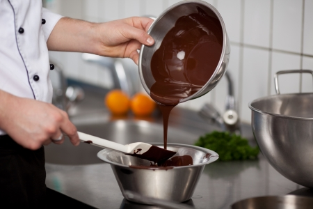 spatula: Closeup of young chef pouring liquid chocolate in bowl at commercial kitchen counter