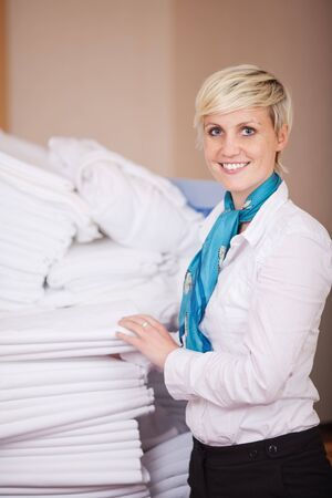 Portrait of young female housekeeper stacking sheets in stock room Stock Photo - 21217544