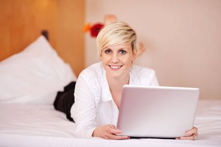 Portrait of young businesswoman with laptop while lying on bed Stock Photo - 21217545