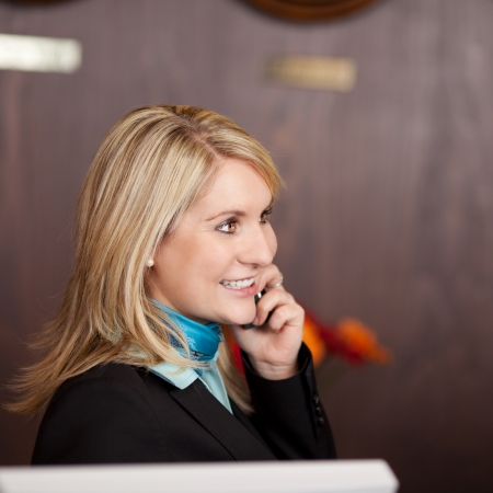 cheerful receptionist using telephone at hotel counter photo